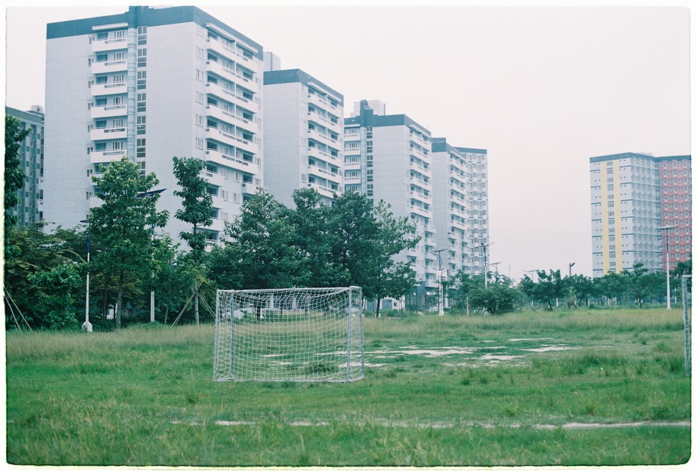 in distant photo of white sports goal on grass field
