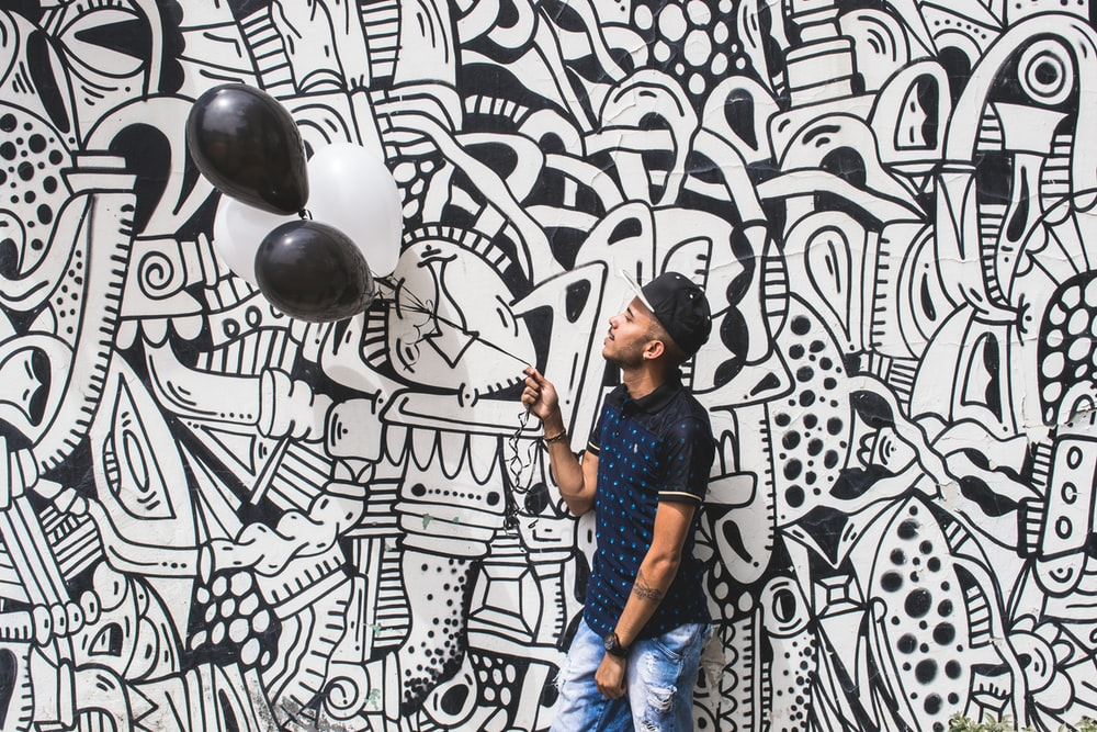 man holding two black balloons
