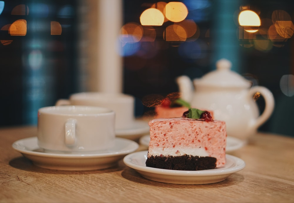 slice of cake near cup on table