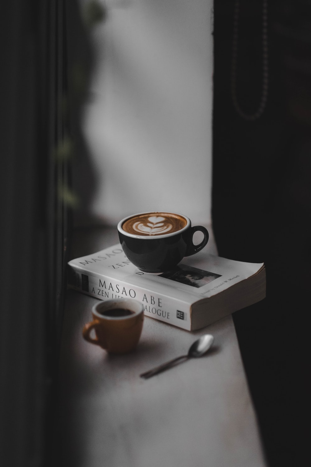 latte filled black teacup on top of book near brown cup on window