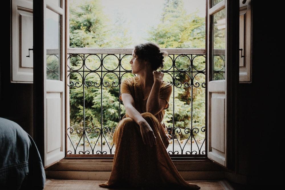 woman sitting on floor near window at daytime