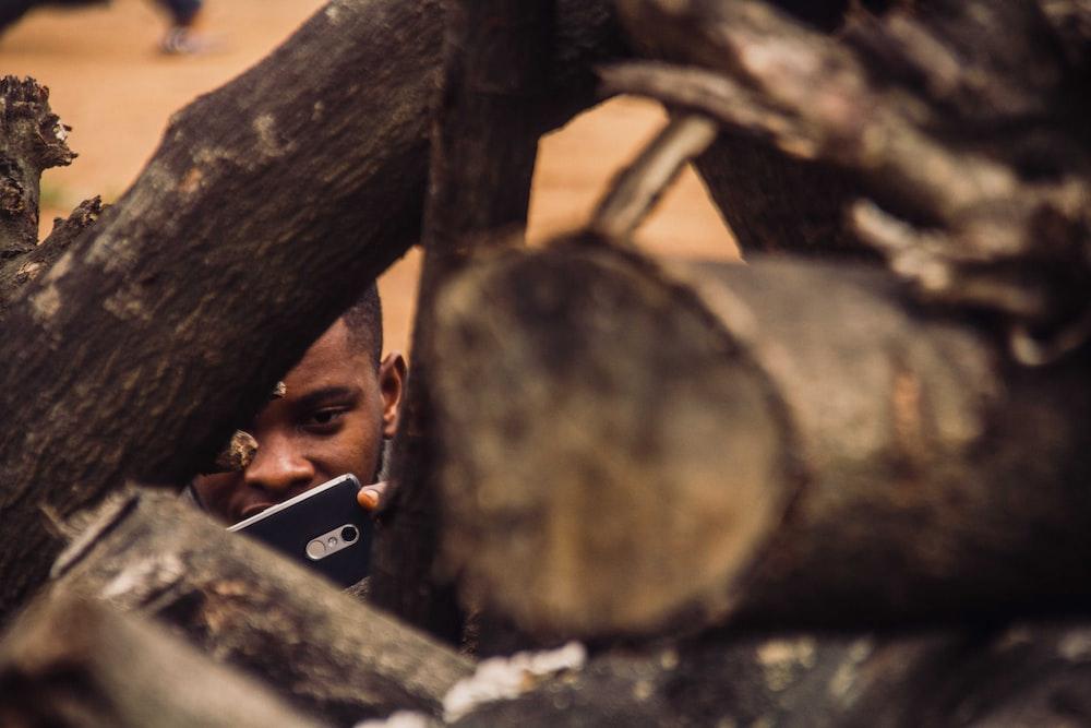 man taking photo of tree logs