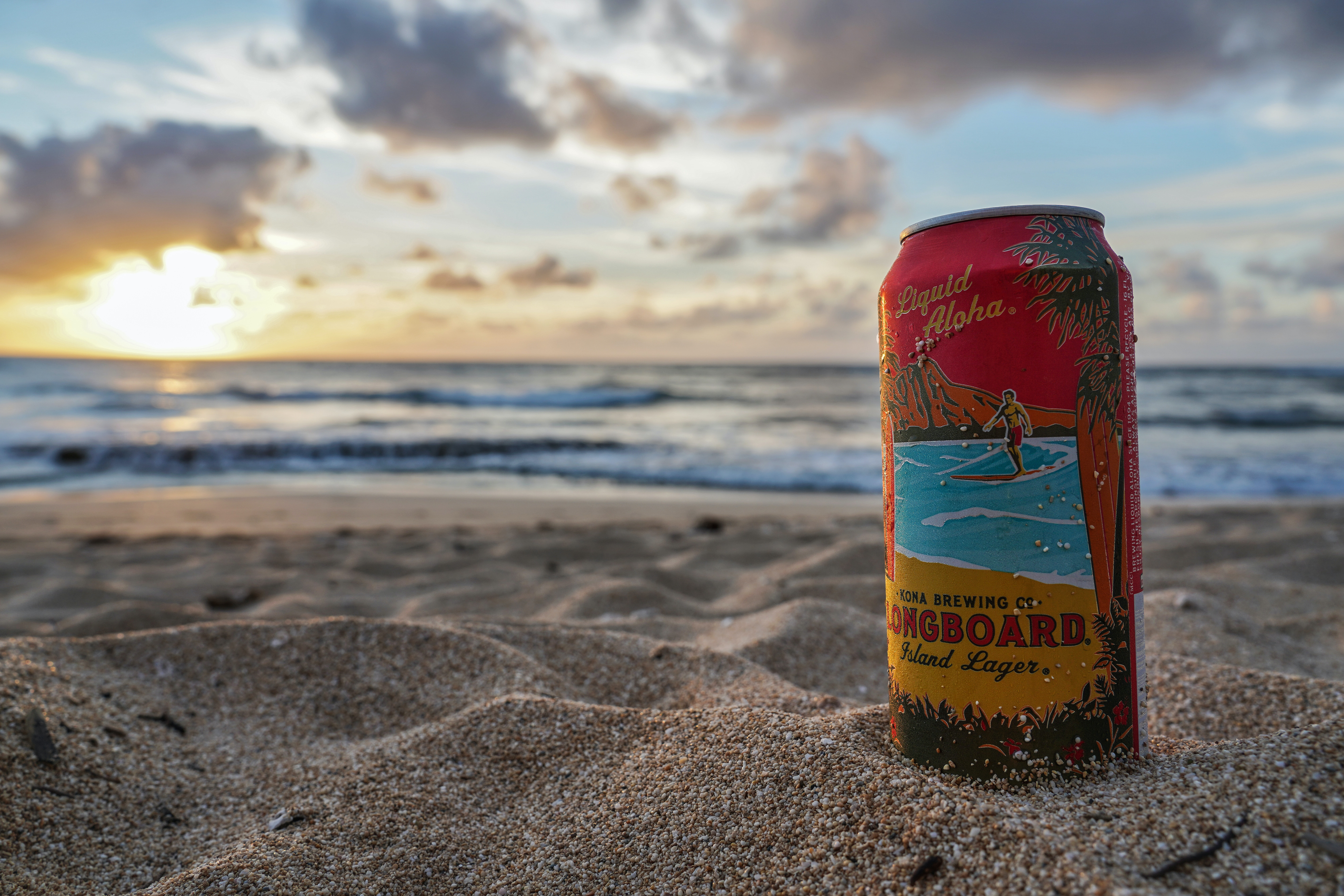 Longboard beverage can on sand by the beach during day