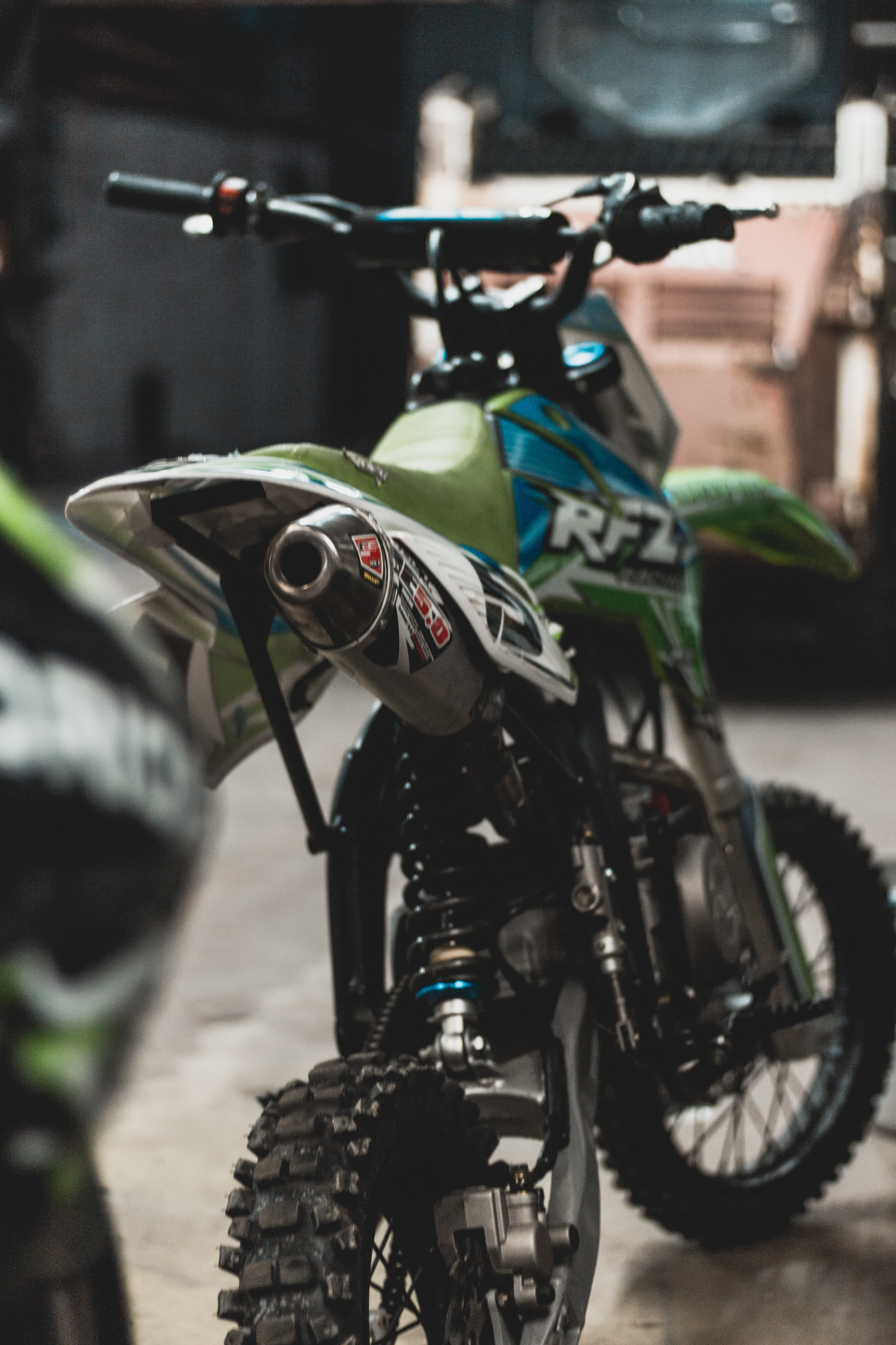 green, blue, and white RFZ dirt bike on gray surface