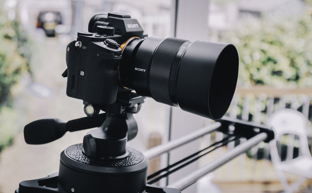 black DSLR camera on mount in selective focus photography