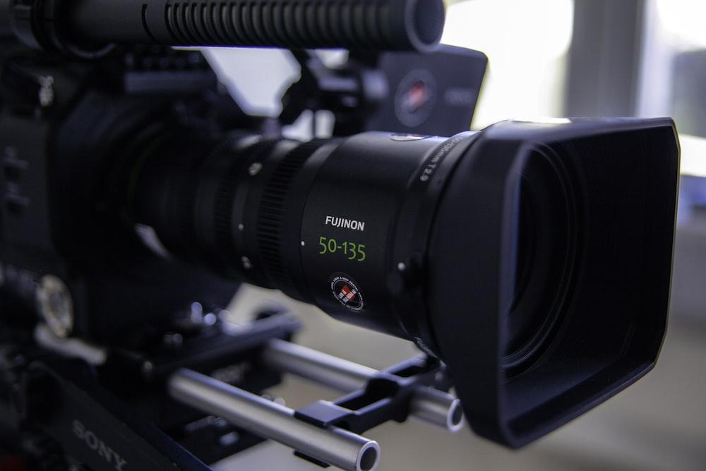 black shoulder-mount camera near brown surface