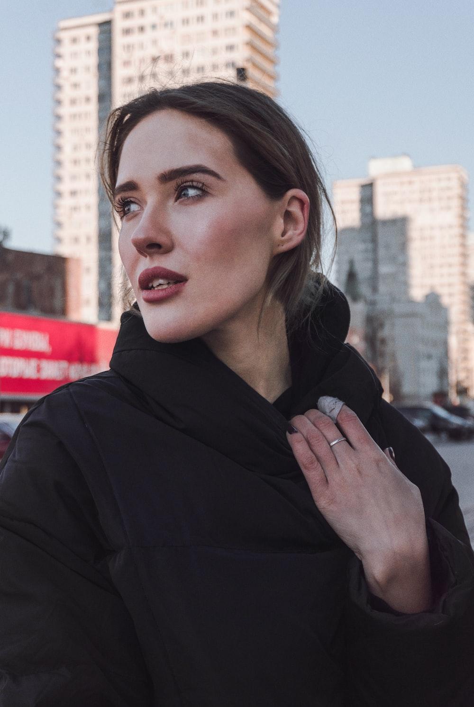 woman wearing jacket near buildings
