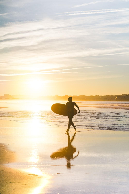man holding surfboard at seaside