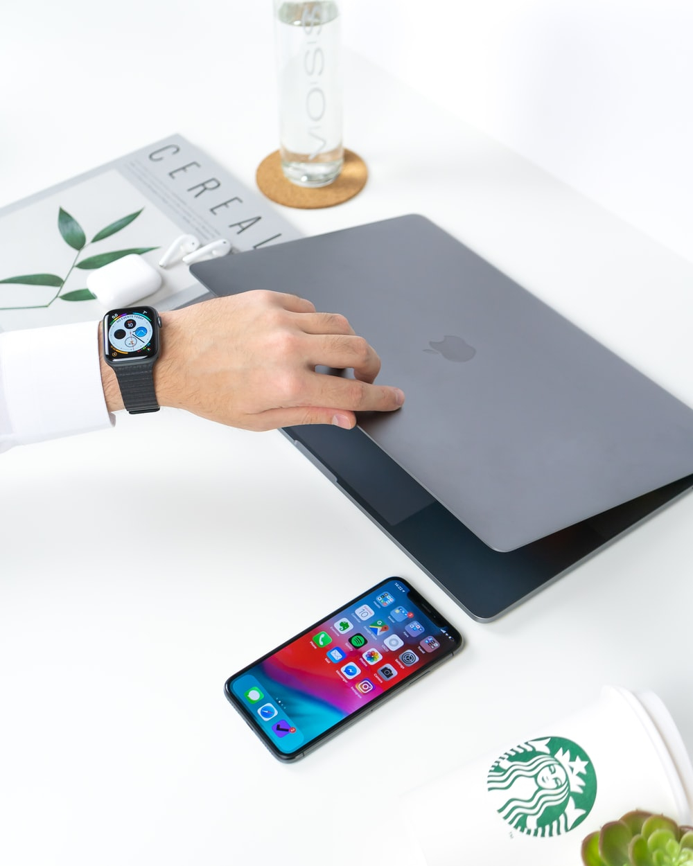 person opening gray MacBook beside iPhone on white wooden table