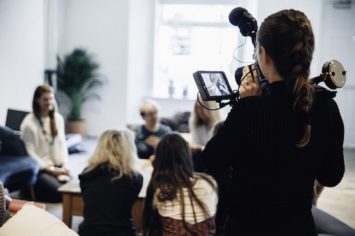 woman holding camera standing near people