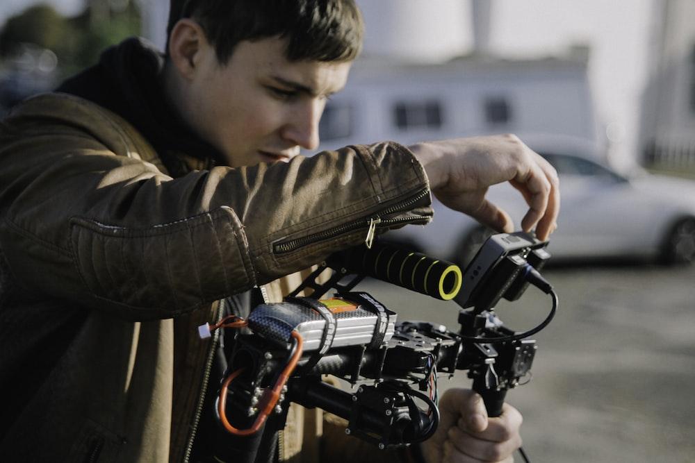 person operating black camera on gimbal at daytime