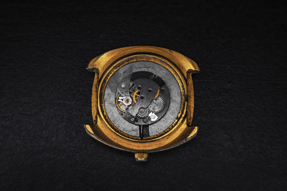 round gold-colored skeleton watch