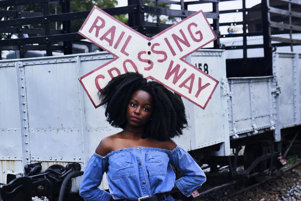 woman standing near railway sign