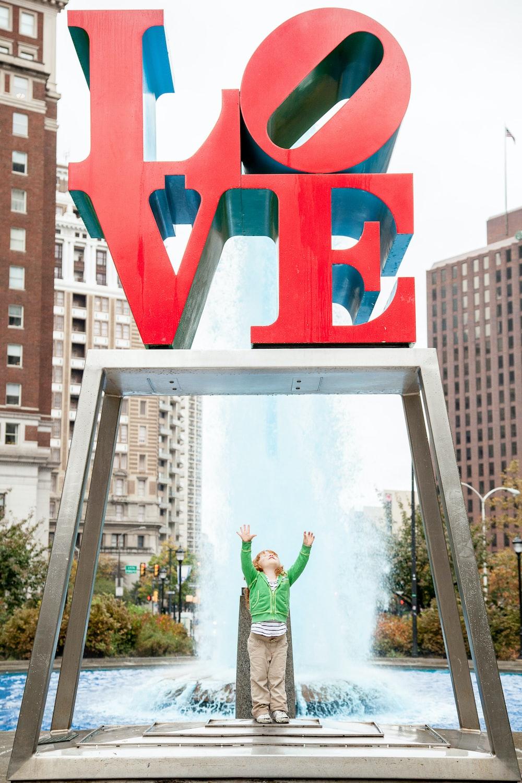 girl standing under love sign near fountain