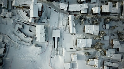 aerial view photo of snow capped houses space station teams background