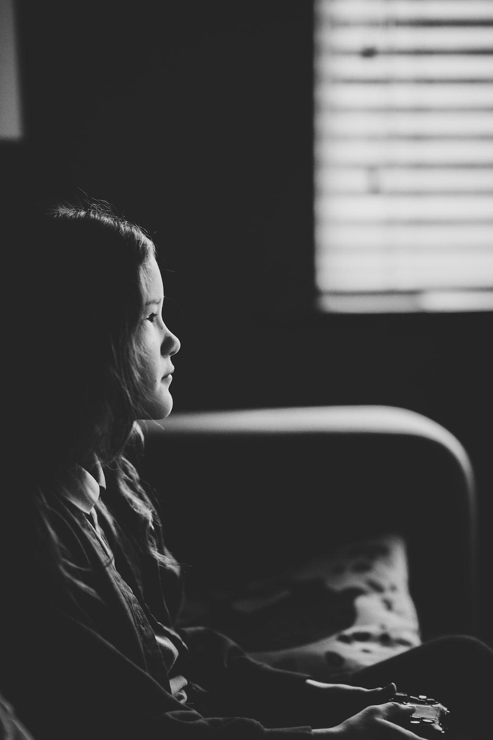 grayscale photo of girl sitting on sofa