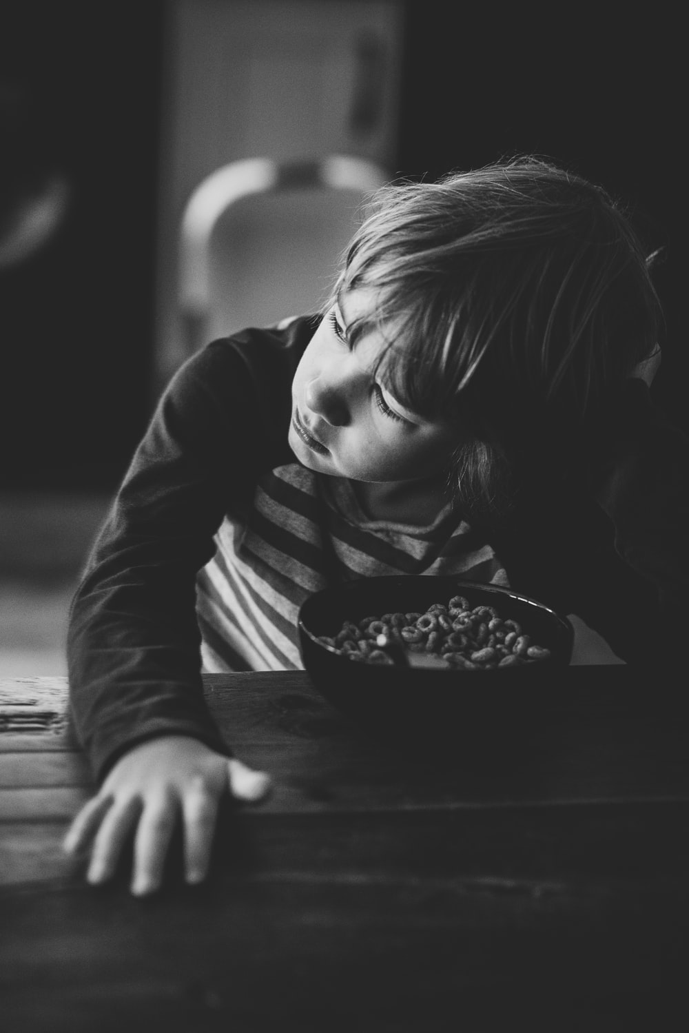boy sitting by the table with bowl of cereals