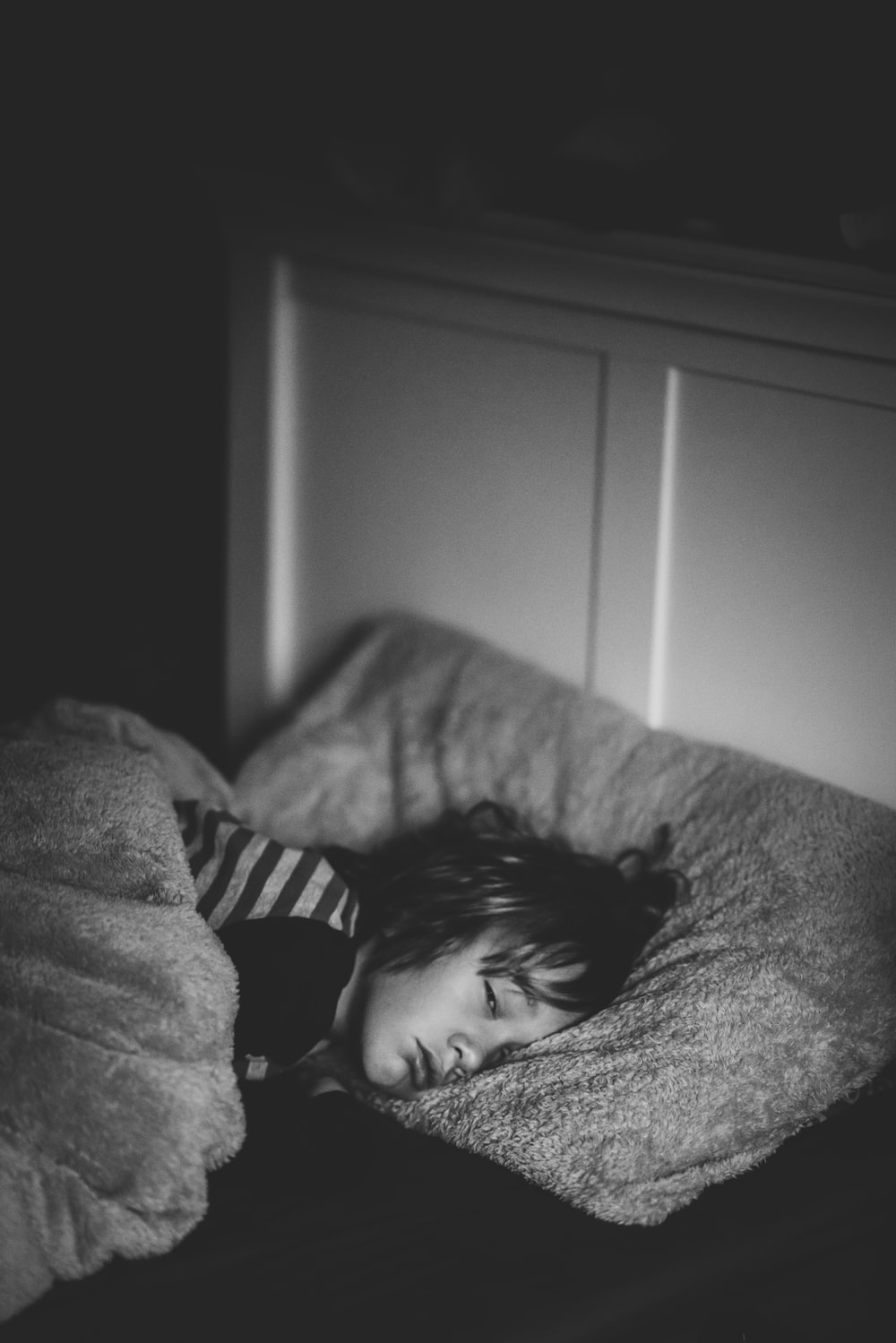 grayscale photography of kid lying on bed