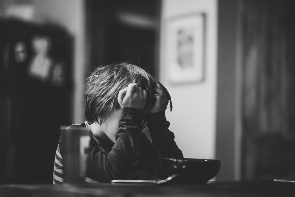 grayscale photography of boy sitting beside table