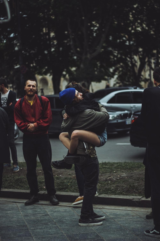 man hugging woman while standing on sidewalk at daytime