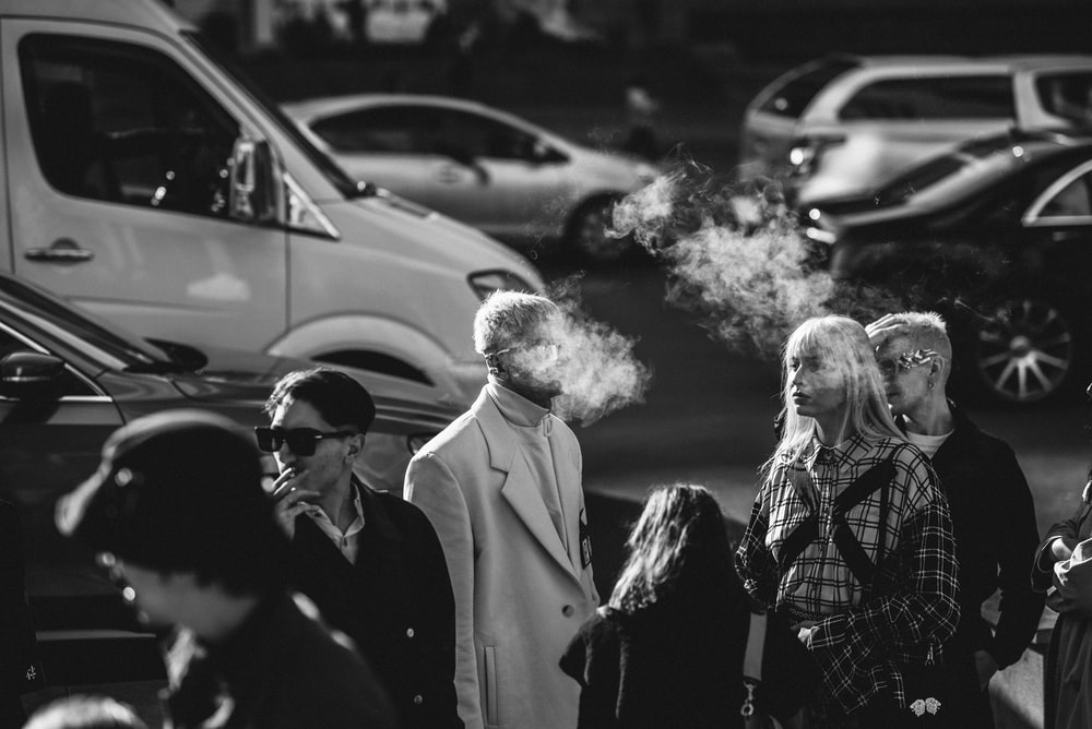grayscale photography of man smoking beside woman