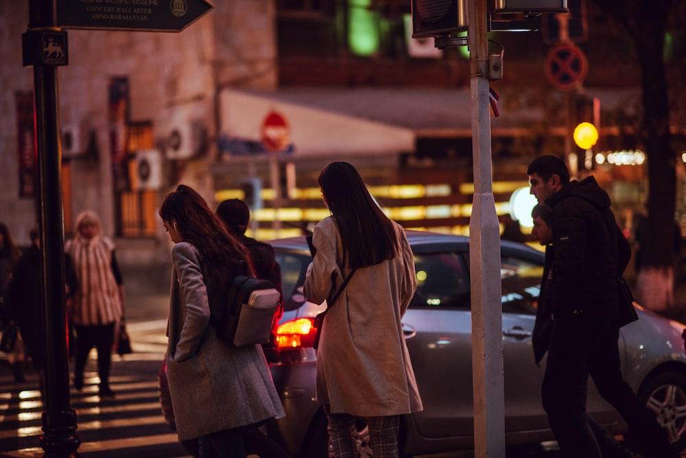 people passing on pedestrian lane near gray 5-door hatchback at night time