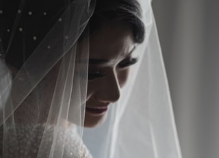 woman wearing white sheer wedding dress standing inside room