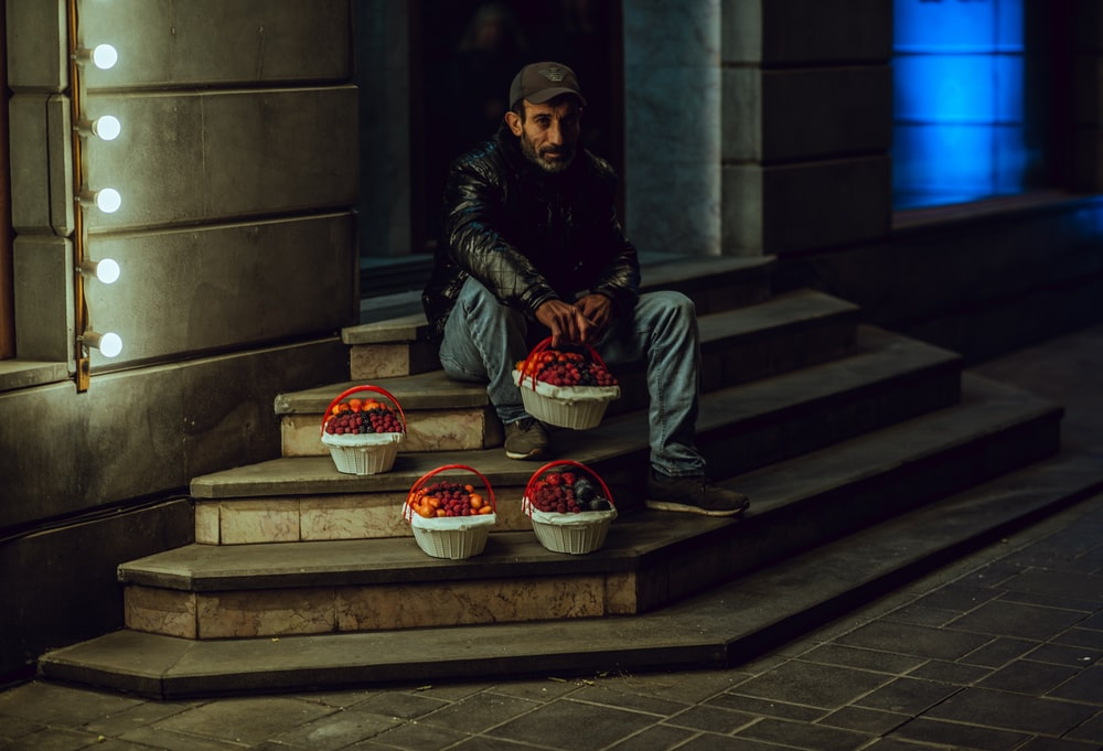 man sitting on stairs holding basket at night time