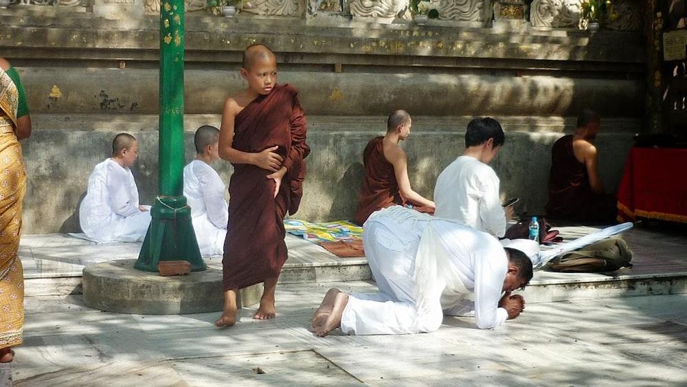 man kneeling on ground beside monk at daytime