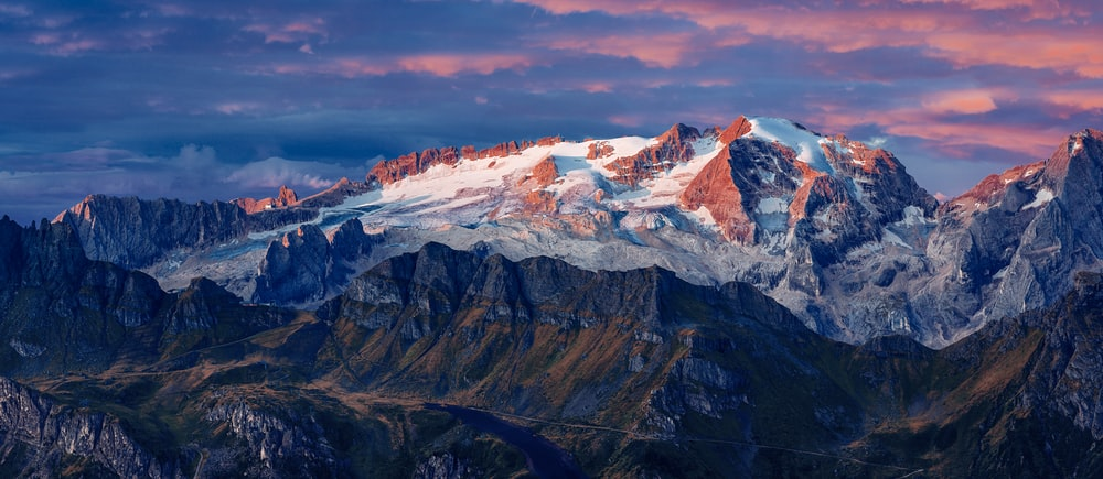 aerial photography of hills overlooking snow capped mountain at daytime