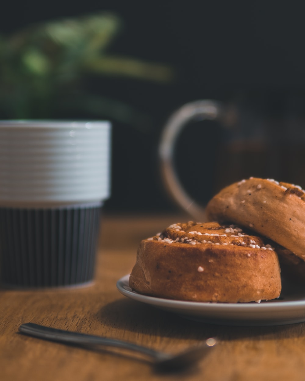 pastry bread with spoon beside and cup