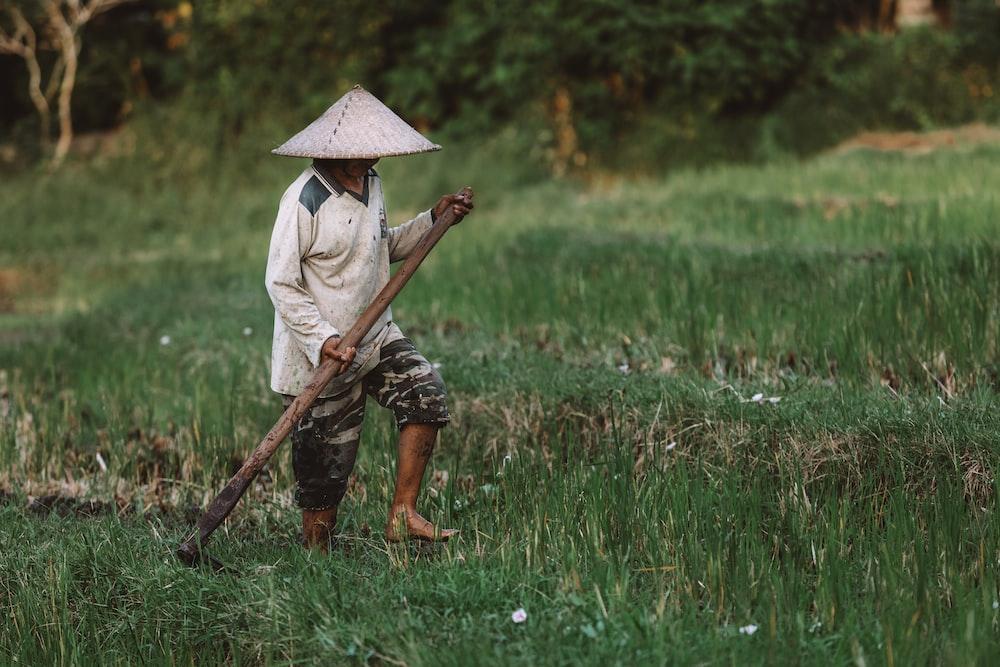 man wearing brown hat standing on grass field