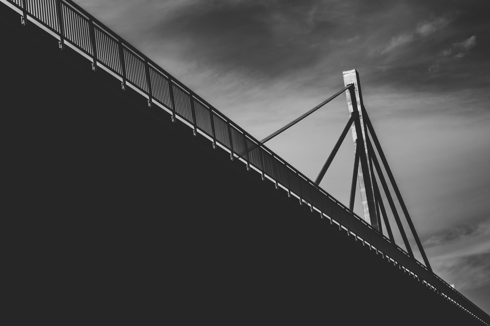 grayscale photography of cable bridge