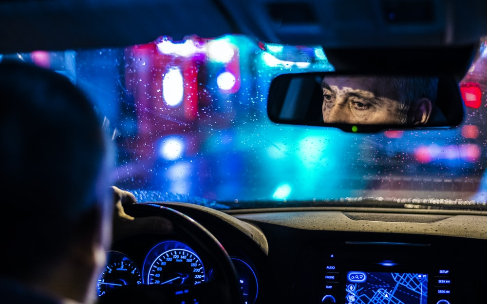 reflective photo of man in rearview mirror