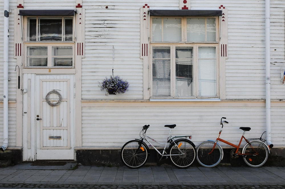 two bicycles parked beside house