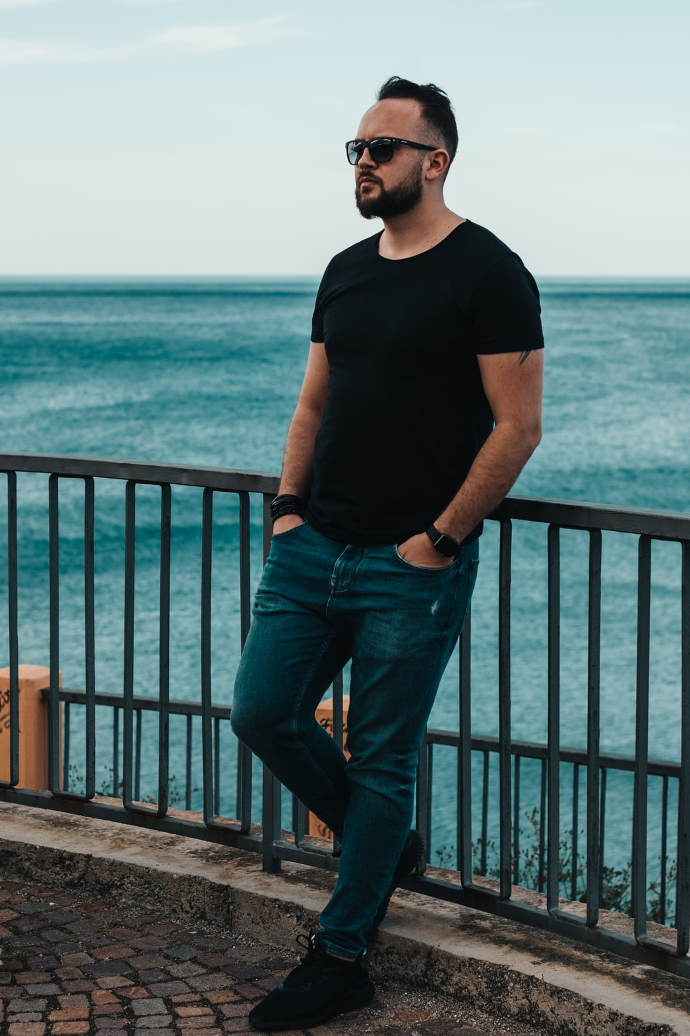 man in black tee shirt and jeans leaning on railings