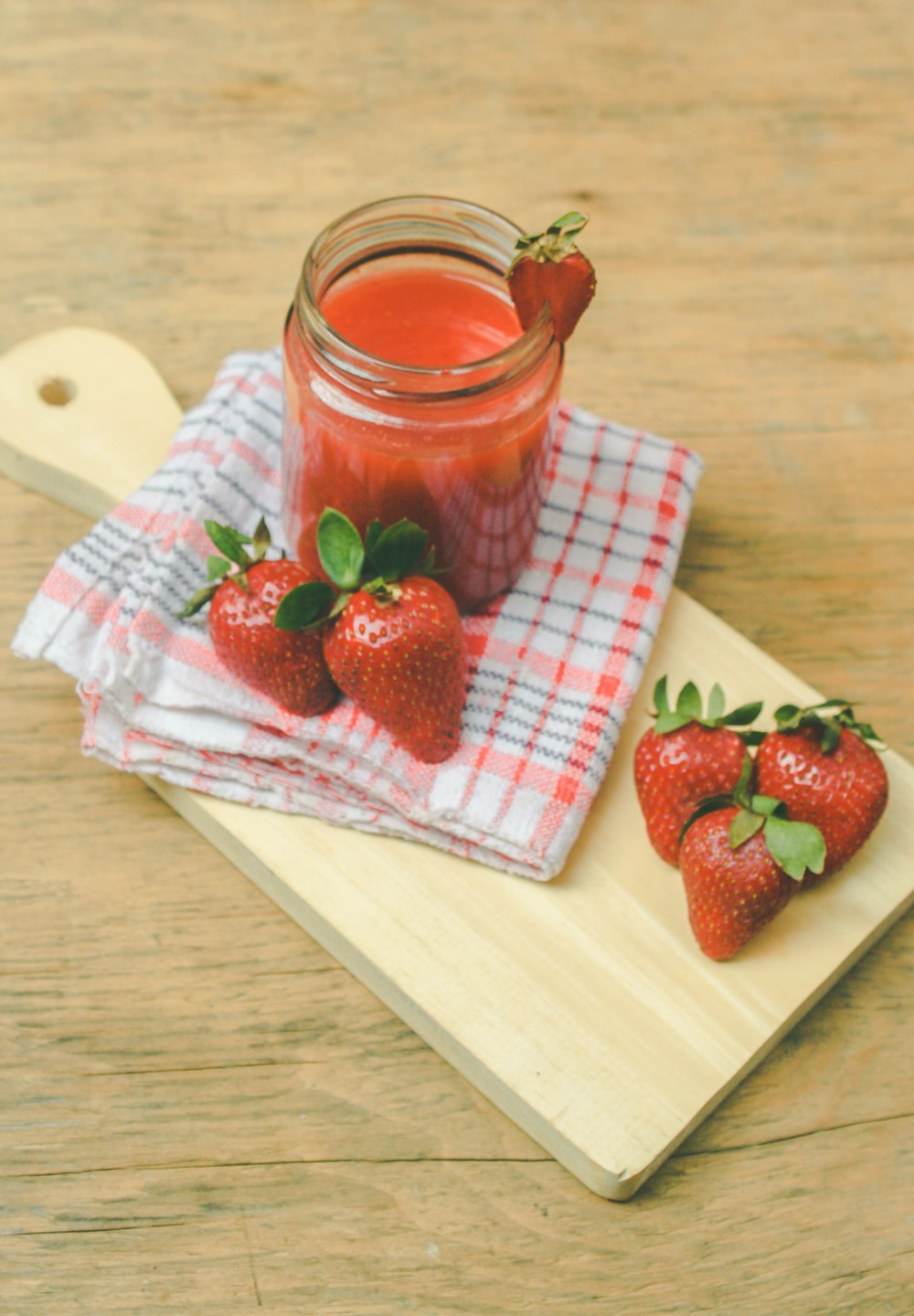 red strawberries on brown chopping board