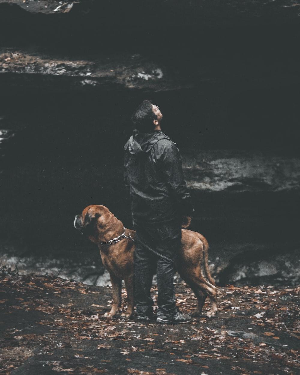 man standing beside dog near rock
