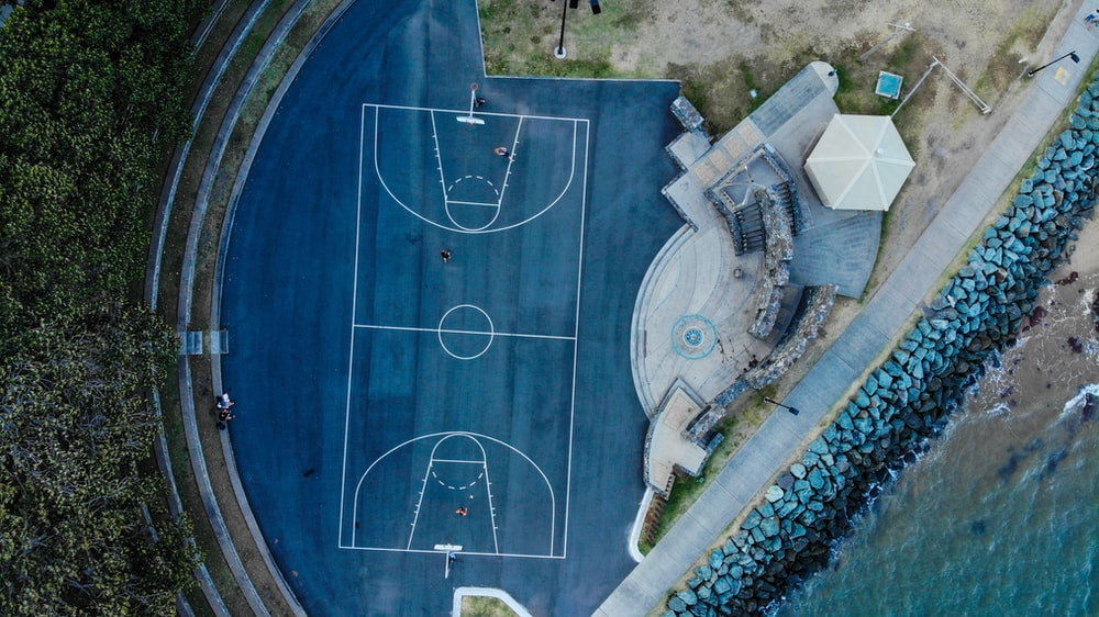 blue floored basketball court by the beach