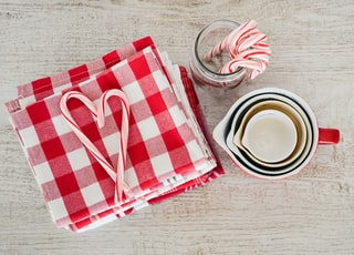 white ceramic mugs beside red and white checked textile
