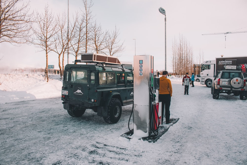 black Land Rover Defender stopping at gas station during winter in iceland