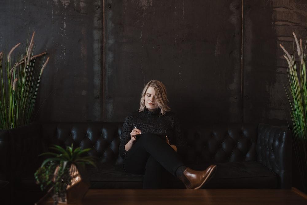 woman sitting on black sofa