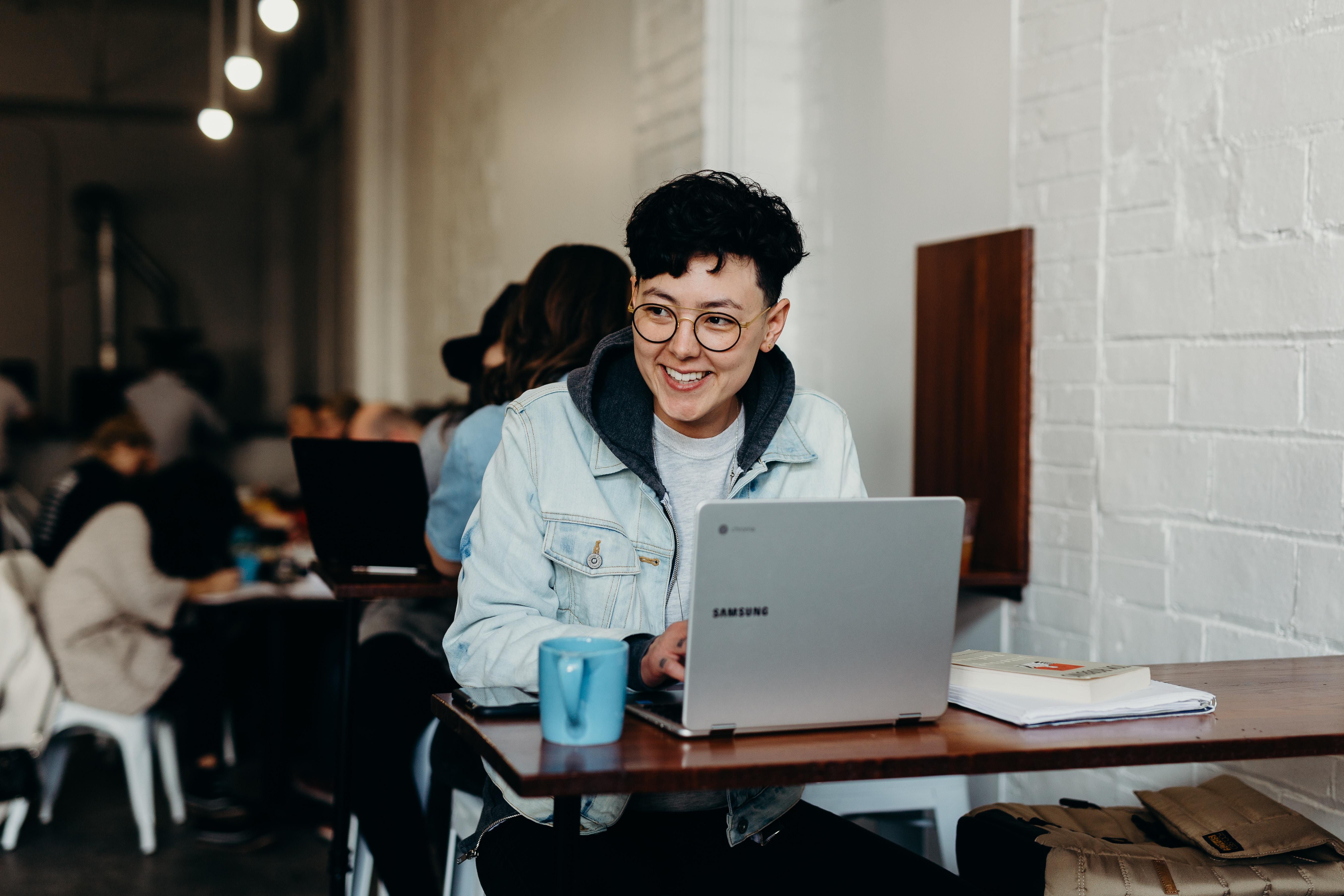 smiling man sitting and using Samsung laptop near people