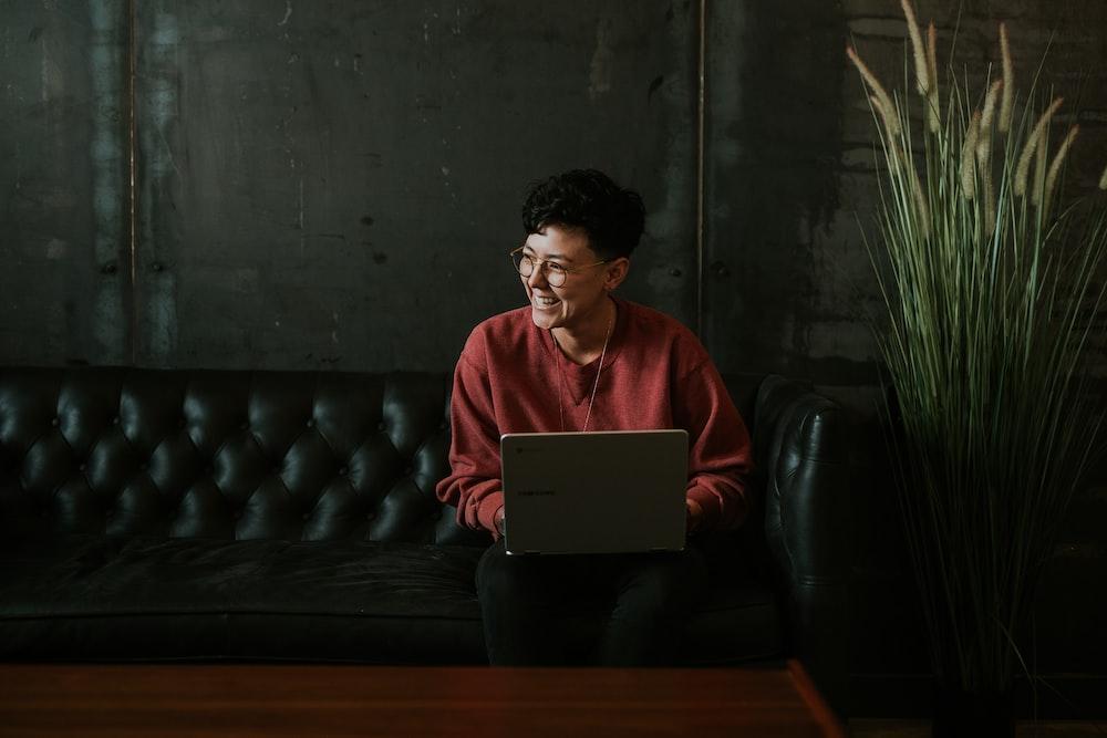 smiling man using laptop computer while sitting on black leather sofa