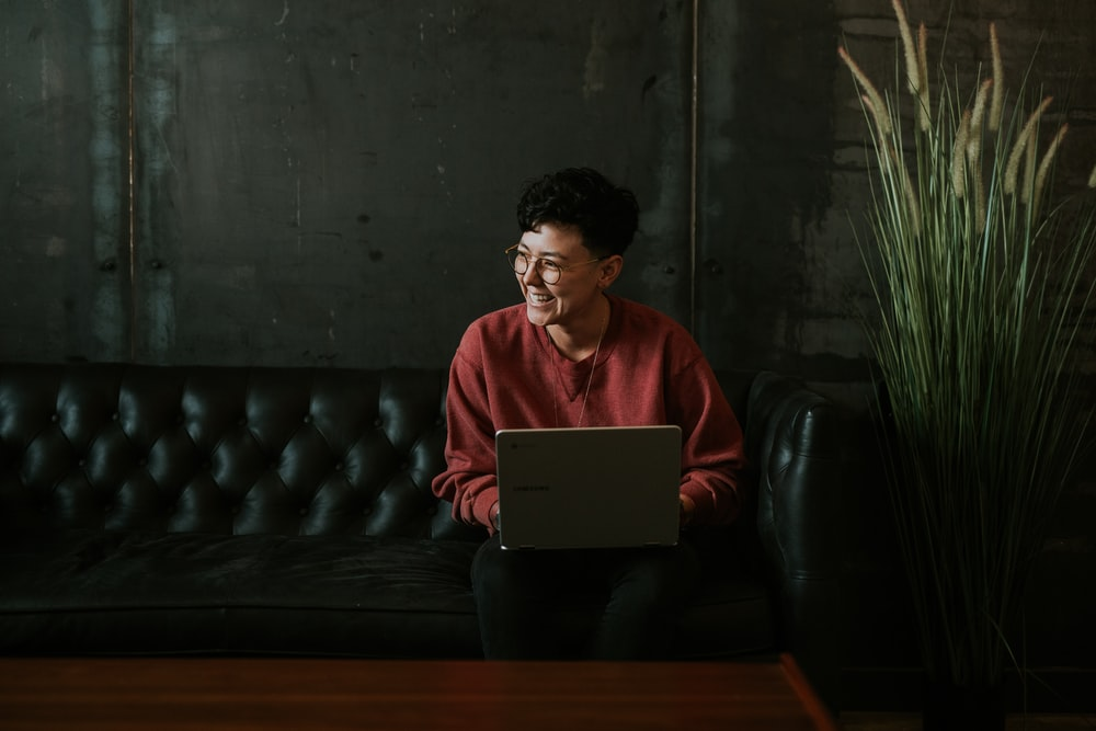 smiling man using laptop computer while sitting on black leather sofa