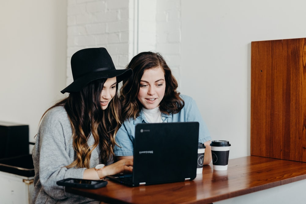 two woman sitting near table using Samsung laptop
