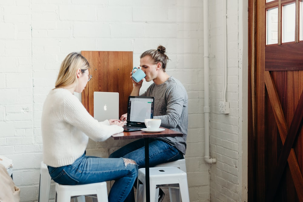 man and woman sitting and using laptops near closed door