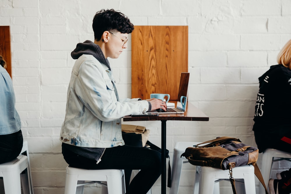 person sitting on chair using laptop