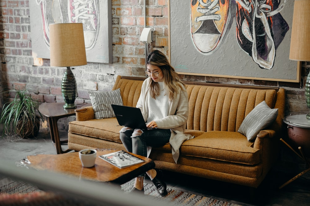 woman using laptop while sitting on chair