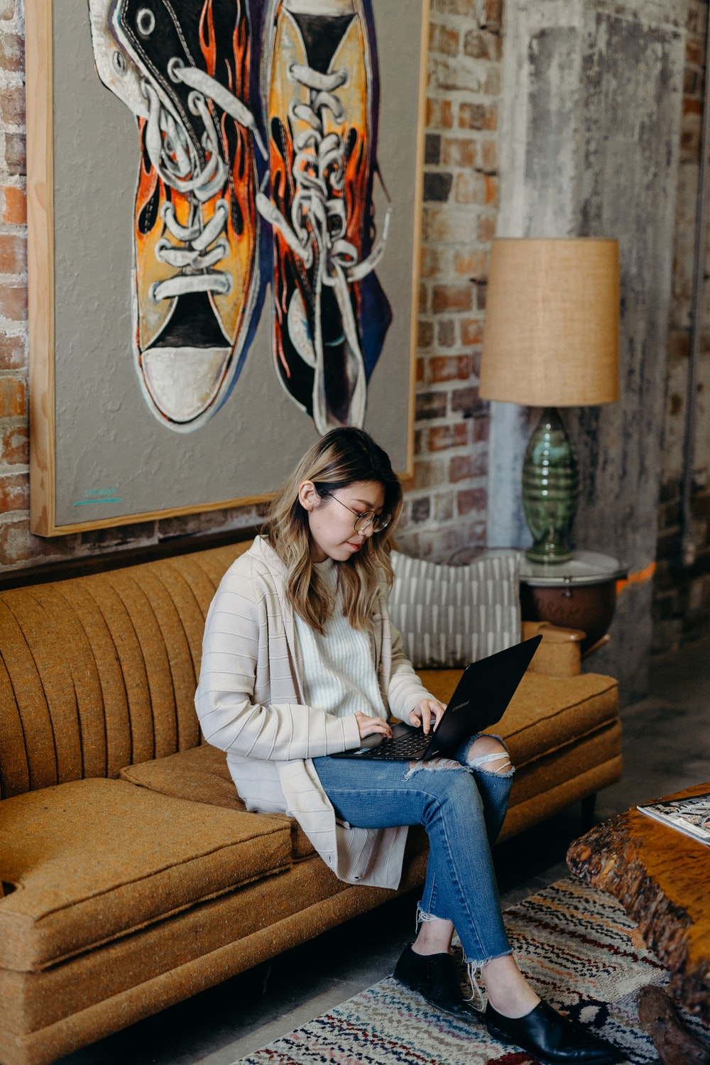 woman using laptop sitting on couch